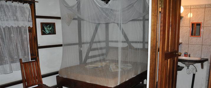 Coco Logo Lodge Caraïbes Sud Puerto viejo de Talamanca chambre en bois rustique avec lit double moustiquaire salle de bain